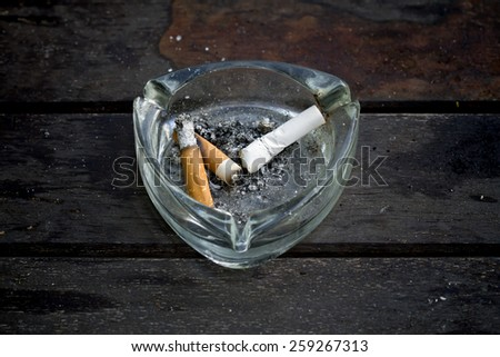 The concept of quitting successfully, cigarette butts into the PB. Dropped in to write a cigarette on a wooden table,No smoking - stock photo