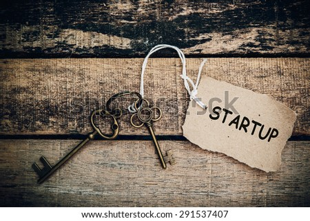 The concept of 'startup' is translated by key and silver key chain - stock photo