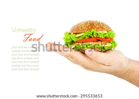 The concept of unhealthy diet, harmful food, overweight, weight loss, diet. Man's hand holding a burger isolated on white background, close up - stock photo
