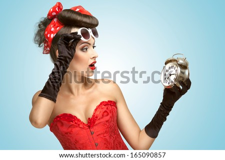 The conceptual photo of a pin-up girl in glamour underwear and gloves watching at the clock. - stock photo