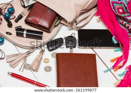 the contents of the female handbag - wallet, keys, phone, lipstick, perfume  - stock photo