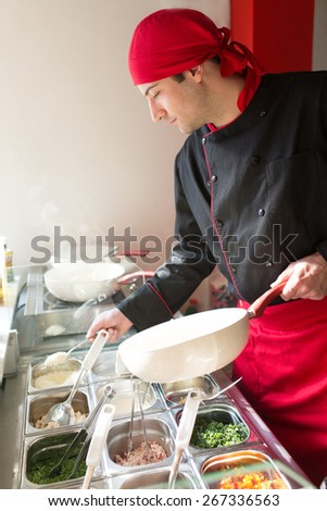 The cook at work in the kitchen - stock photo