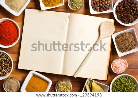 The cookbook and various spices and herbs. - stock photo