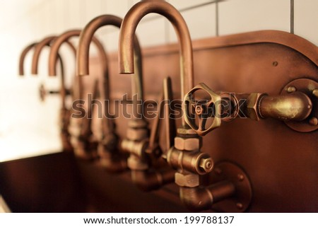 The copper taps on an old brewery - stock photo