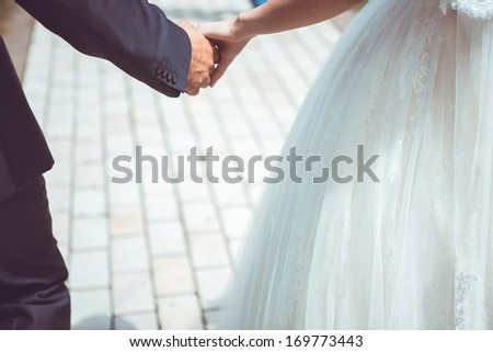 The couple on a walk firmly hold on to the hands. There are the first steps of newly-weds one-way. Holding on to the hands they create the silhouette of heart of their love - stock photo