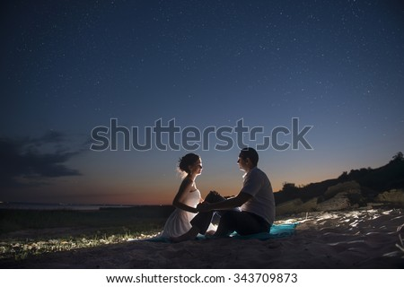 The couple on the seashore at night - stock photo