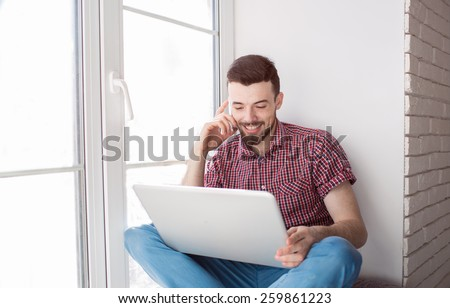 The courageous, handsome, a student working on a windowsill with a laptop. worker communicating on the Internet. Funny man  play for laptop - stock photo