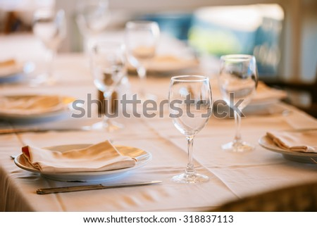 The cozy interior of summer cafe - sheltered tables with tablecloths. European town - stock photo