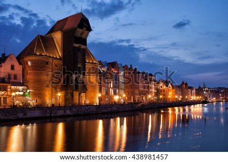 The Crane in city of Gdansk in Poland by night, Old Town skyline from Motlawa River - stock photo