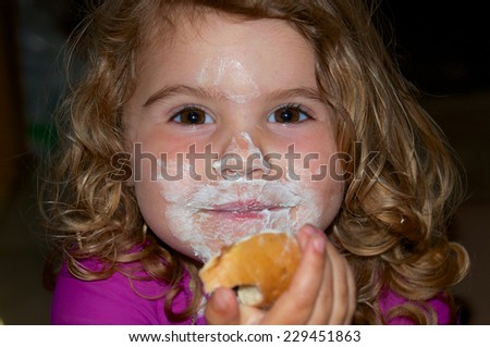 The cream cheese looks better all over my face than on the bagel - stock photo