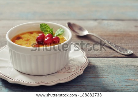 The creme brulee in ceramic baking mold with mint and berries on wooden table - stock photo