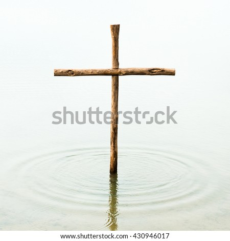 The cross is standing in the water, symbol for washing off our sins by Jesus, who died on the cross for all people - stock photo