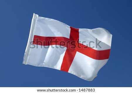 The cross of St George, the flag of England, isolated against a clear blue sky. Motion blur at the tip of the flag. - stock photo