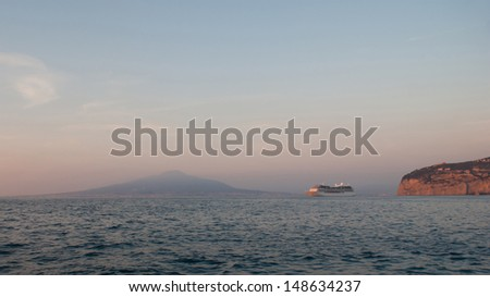 The cruise ship arrives to Sorrento at sunset, Vesuvius mount on the background, Italy. - stock photo
