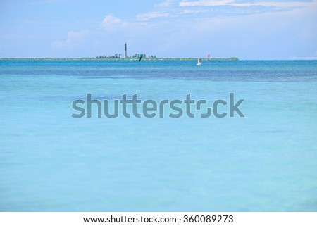 The crystal clear and shallow waters on the islands of the tropical Dry tortugas with the Loggerhead key lighthouse in the background on a separate island - stock photo