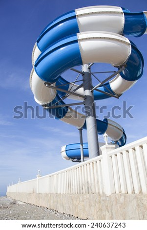 The curved water slide built straight on a beach in resort town Payallar (Antalya's Province, Turkey). - stock photo