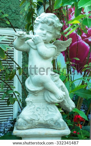 The cute statue playing flute instrument in the garden - stock photo