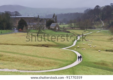 The Dales Way footpath as it winds its way serenely past Bolton Abbey in the Yorkshire Dales towards Windermere in the Lake District - colour with walkers - stock photo