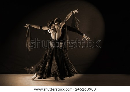The dancers in ballroom against on black background - stock photo