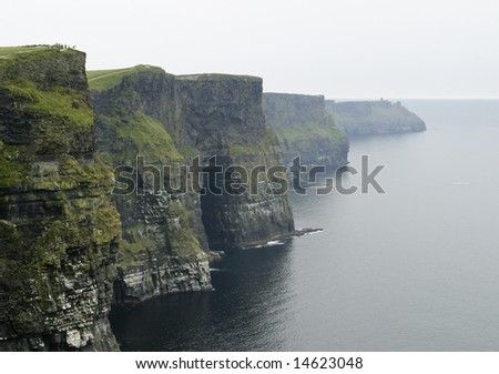 The dark, ominous Cliffs of Moher are a landmark in Western Ireland with sheer rock walls that rise 600 feet from the ocean. A group of people in the field at the upper left provide a sense of scale. - stock photo