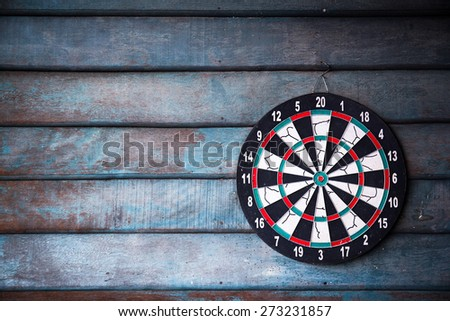 The darts isolated on wooden background - stock photo