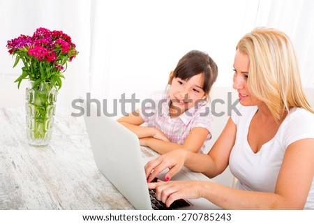 The daughter eating chocolate while her mother is working on a Laptop computer. - stock photo