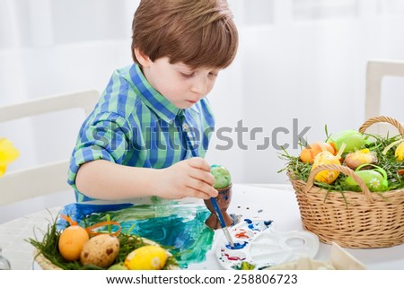 The day before Easter, beautiful child painting eggs for easter - stock photo