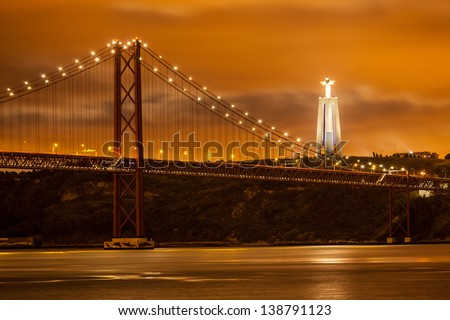 The 25 de Abril bridge over Tagus river and big Christ monument in Lisbon at night, Portugal - stock photo