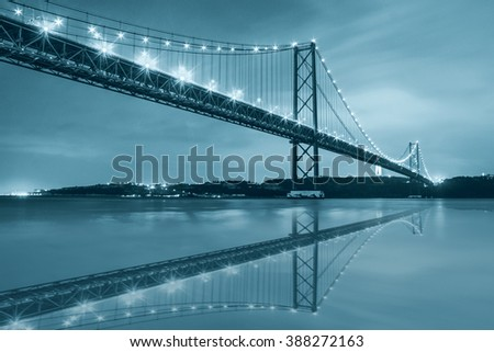 The 25 de Abril bridge over Tagus river and big Christ monument in Lisbon, Portugal, black and white blue toned with reflection in water - stock photo