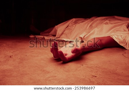 The dead woman's body. Focus on hand, red tone color processed - stock photo