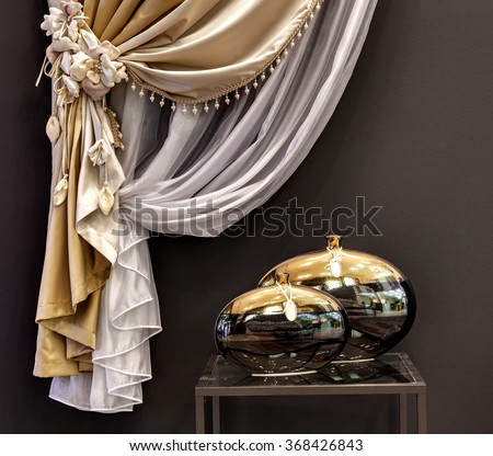 The decorated gold curtain and little table with two vases - stock photo