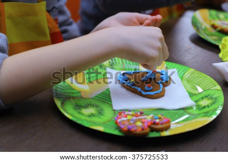 the decoration of the homemade heart-shaped cookies by kids on master-class - stock photo