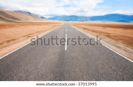 The desert road and the mountains on the horizon - stock photo