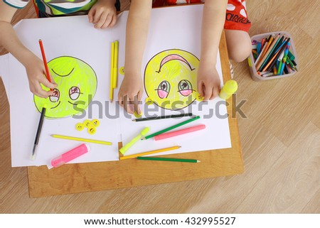 the development of emotional intelligence. child psychology. girl and boy depict different emotions. the girl and the boy draw happy and sad emoticons - stock photo