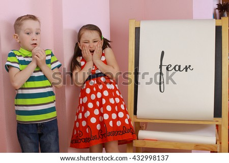 the development of emotional intelligence. child psychology. girl and boy depict different emotions. against the background of the drawing board - stock photo