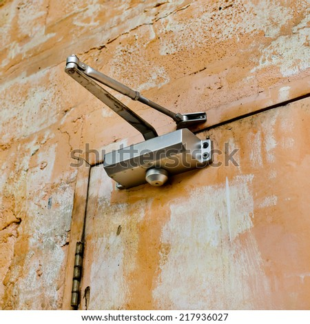 The device for automatic closing a door with old and rust door and wall - stock photo