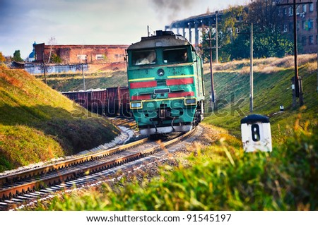 The diesel train with wagon goes on a curve. Cargo transportation in tanks by rail - stock photo