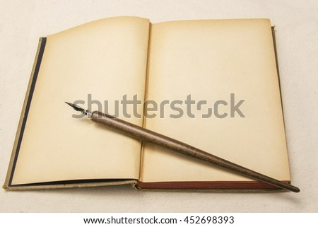 The dip pen on brown book - stock photo