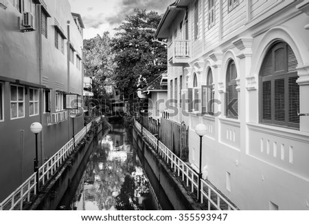 The ditch between vintage houses / Black and white - stock photo