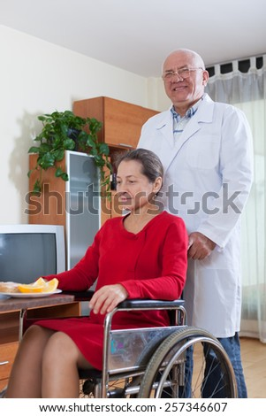 The doctor brings up   disabled woman to the dinner table. - stock photo