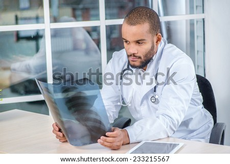 The doctor examines the medical evidence. Confident doctor looking at an X-ray while sitting at a desk in the office - stock photo