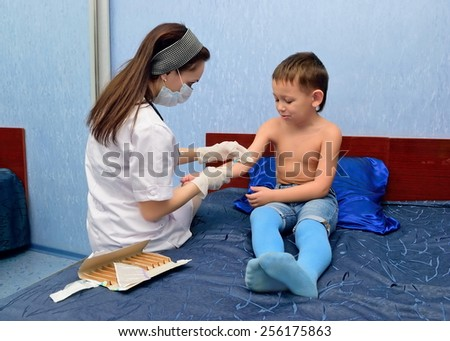 The doctor makes a shot the boy at home - stock photo