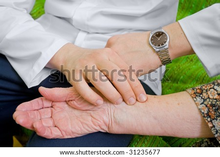 The doctor measures old lady's blood-pressure - stock photo