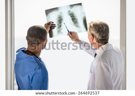 The doctors looking at an x-ray results in hospital. - stock photo
