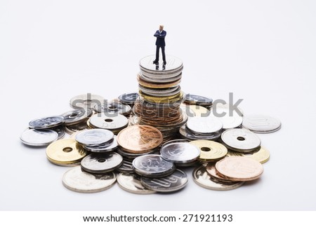 The doll business man on top of the stacked coins - stock photo