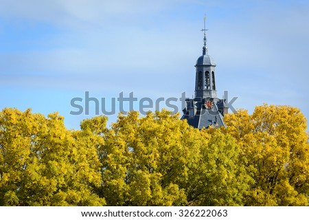 The dome  of Drommedaris historic gate  over the crowns of golden ash in Enkhuizen, The Netherlands - stock photo