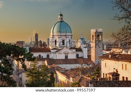 the dome of the Duomo Nuovo cathedral, old palaces and modern buildings in Brescia immediately after sunrise - stock photo