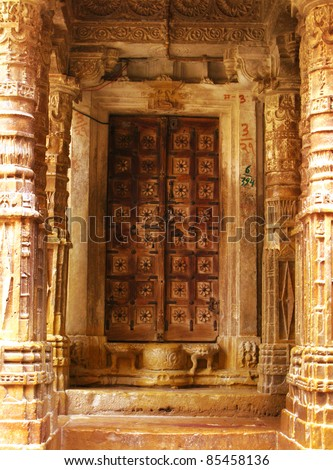 "The door of an ancient jainist temple in Jaisalmer, the magnificent ""Golden City"" in the heart of Rajasthan (India), surrounded by the desert of Thar. - stock photo"