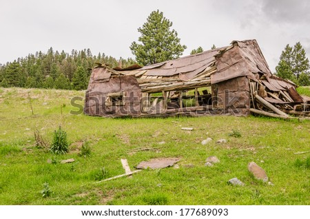 The dreary sky makes a perfect background for this sad, abandoned home - stock photo