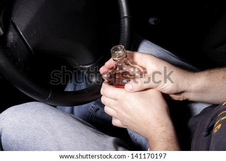 The driver drinking alcohol in the car - stock photo